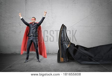 A smiling businessman in a superhero red cape with hands raised in success motion standing beside a giant human foot. Business and success. Unexpected problems. Rivalry and confrontation.