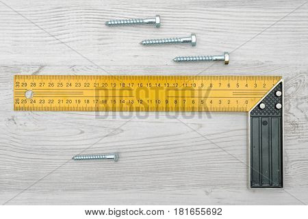 A yellow angle ruler and four metal bolts horizontally placed on white wood background. Building and construction. Engineering. DIY tools.