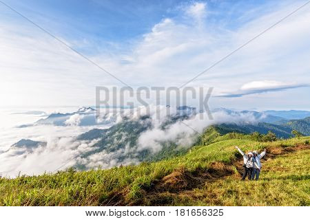 Two female tourists mother and daughter stand waving amidst the beautiful natural landscape of mountain range sky cloud and fog in the winter at Phu Chi Fa Forest Park Chiang Rai Thailand