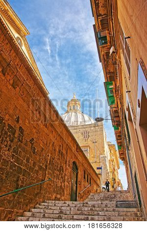 Valetta, Malta - April 5, 2014: Street with staircase and dome of Carmelite Church in Valletta old town Malta