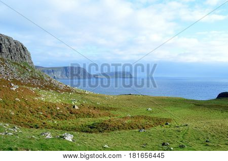 Rugged landscape and sea cliffs along the rocky shore of Neist Point in Scotland.