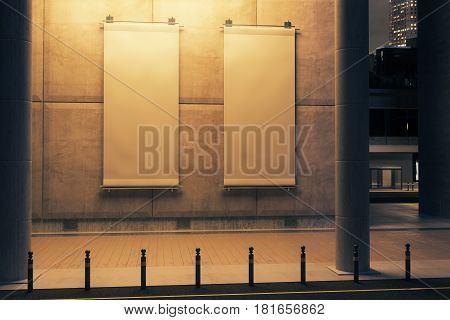 Two blank illuminated vertical posters hanging on concrete building. Nighttime. Ad concept. Mock up 3D Rendering