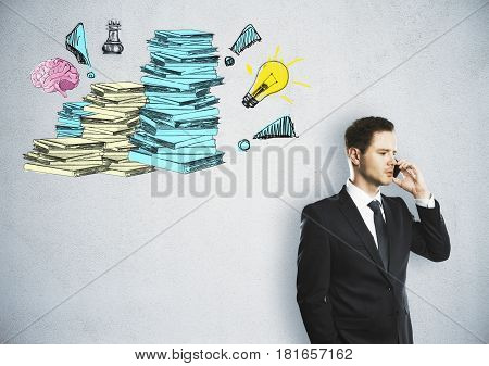 Handsome young businessman talking on the phone on concrete background with drawn paperwork stacks. Workload concept