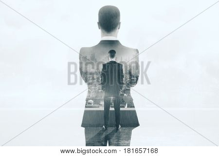 Back view of thoughtful young businessman on rooftop with city view. Career concept. Double exposure