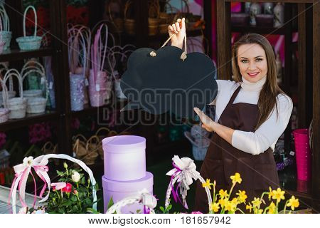 florist-seller points to an empty speech cloud while at work in a flower shop