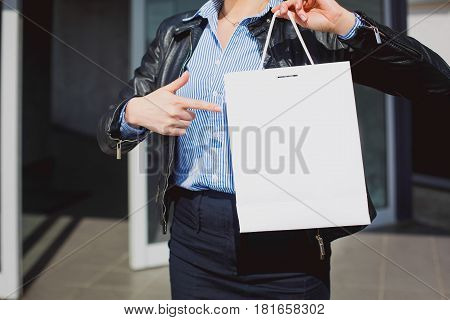 retail concept. Female hand pointing at a blank and white shopping bag. On paper bag space for text