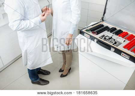 Two optometrists, in white coats stand side by side, near open suitcase with set of trial lenses in ophthalmology clinic.