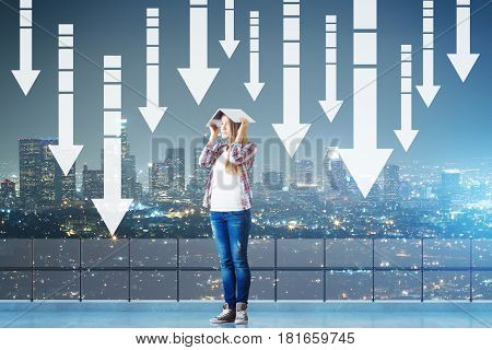 Young woman covering head with book while standing on concrete rooftop with railing night city view and downward arrows. Failure concept