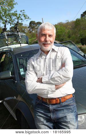 Senior man leaning on carhood