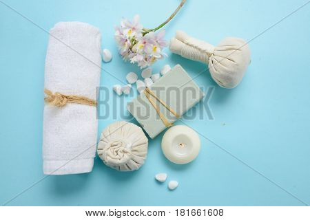Spa concept on blue background with herbal ball, salt in bowl, candle , cherry