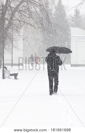 Bad weather in a city: a heavy snowfall and blizzard in winter. Male pedestrian hiding from the snow under umbrella, vertical