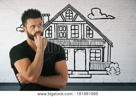 Thoughtful bearded young man in brick interior with drawn house. Real estate and mortgage concept. 3D Rendering