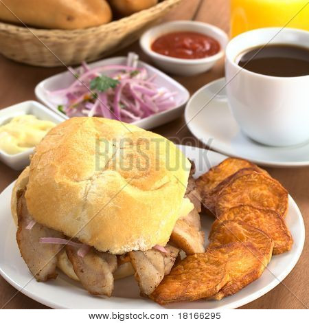 Typical Peruvian breakfast consisting of Pan con Chicharron (Bun with fried meat) and fried sweet potato salsa criolla (onion salad) ketchup mayonnaise with coffee orange juice and buns (Selective Focus Focus on the front of the bun and the meat) poster