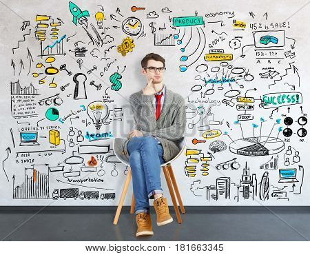 Thoughtful young man sitting on chair in interior with business sketch on wall. Profit concept