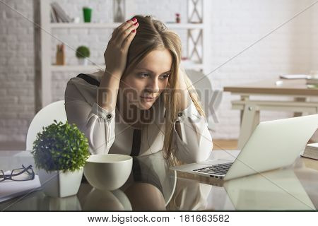 Tired young caucasian woman using laptop at workplace. Workload concept