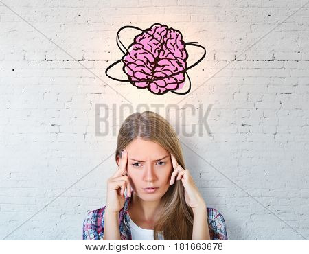 Thoughtful young woman with brain sketch on concrete background. Brainstorming concept