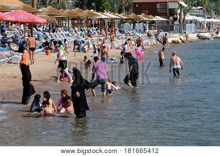 EILAT ISRAEL - NOVEMBER 18 2010: Kids men and women relax on the beach