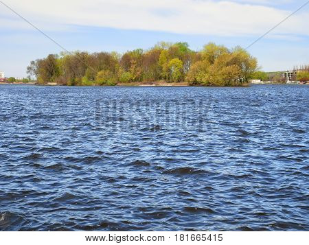Waves on water surface of lake with island in fine spring weather