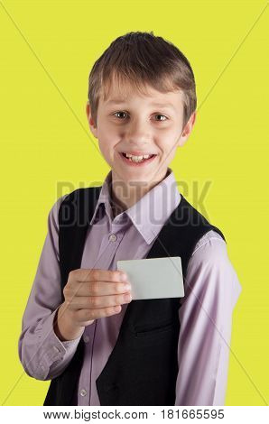 cheerful boy in purple shirt and black waistcoat showing white card. Yellow background vertical photo