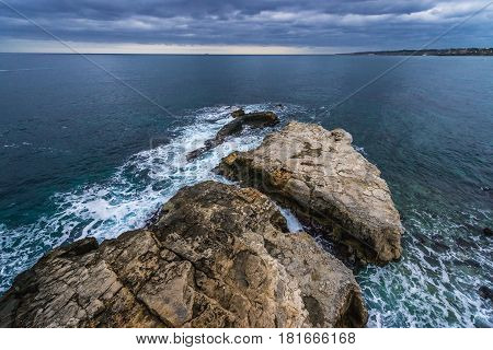 Ionian Sea and larg rocks seen from the old part of Syracuse - Ortygia isle Sicily Italy