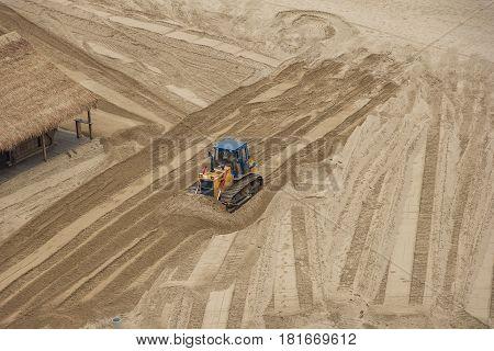 one bulldozer flattens beach sand. top view
