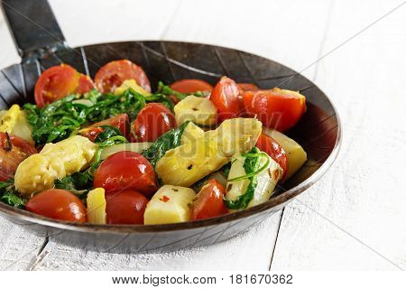 vegetable pan with fried asparagus tomatoes and spinach on a white wooden table low carb meal selected focus narrow depth of field