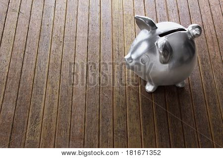 Silver Piggy Bank on a Wooden Background