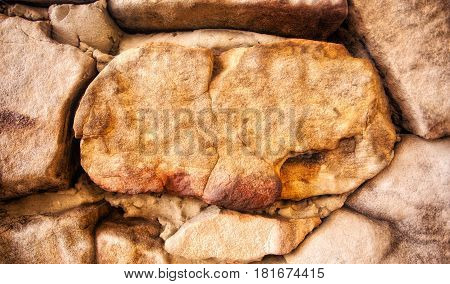 A close up of large rough textured rocks in shades of brown and orange background