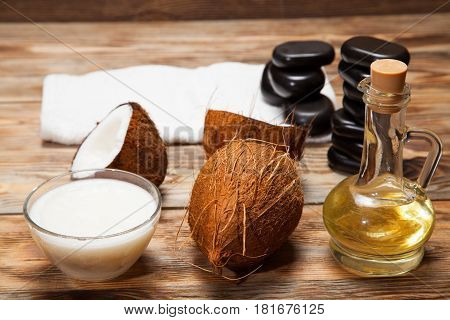 massage oil in glass bowl on wooden table green towel and stones for Spa treatments