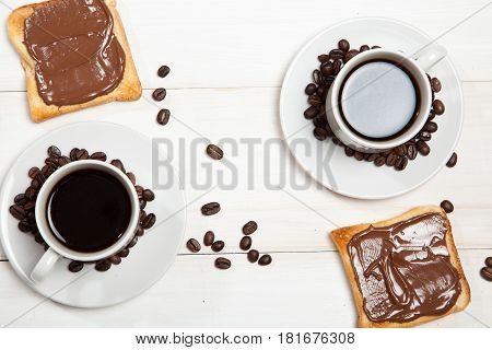 Two cups of coffee and toast with chocolate on a white wooden table