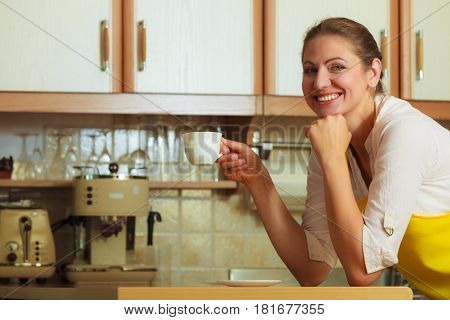 Happy mature woman holding cup of coffee in kitchen. Housewife female with hot energizing beverage. Caffeine energy.