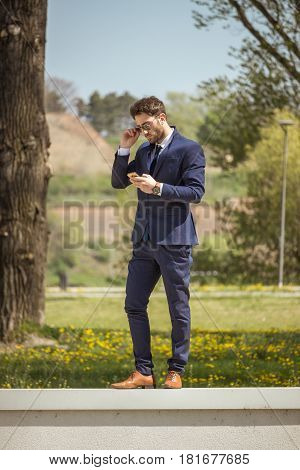One Young Man, Formal Clothes Suit Tie, Using Smartphone, Standing On Wall, Outdoors Nature