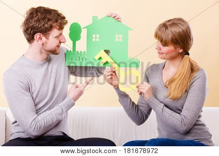 Couple Holding Key And House Cutouts.