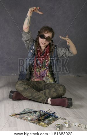 Attractive young female artist with dreadlocks lies on the floor, holds brushes, there are tubes with paints nearby.