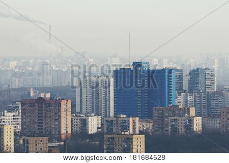 Close-up shooting from high point of residential district in metropolitan city with tall blue building multiple residential houses of different sizes bare trees on winter day and smoking chimneys