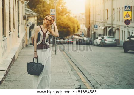 Attractive adult tall caucasian woman in long white skirt sunglasses and with bag is fixing her hair while standing on street during sunny summer day with copy space for your advertising message