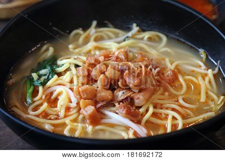 Chinese yellow noodle soaked in a prawn soup base as part of the famous Big Prawn Noodle dish unique in Singapore and Malaysia with toppings of pork lard