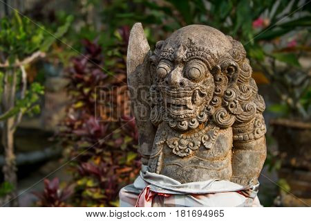 ancient stone deity with a beard, curly hair, round eyes, big teeth and fangs located in the tropical forest of Bali