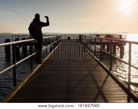 Tourist Sit On Mole Handrail And Takes Pictures.wooden Boardwalk