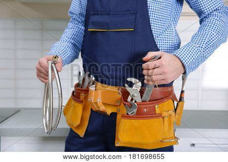 Plumber in blue uniform with tool belt at kitchen, closeup