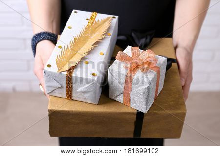 Female hands holding present boxes closeup