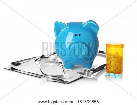 Piggy bank with stethoscope and clipboard on white background
