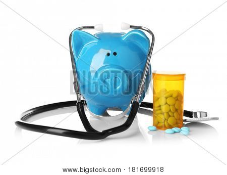 Piggy bank with stethoscope and pills on white background