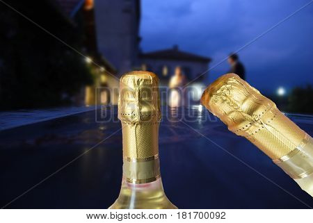 bride and bridegroom at the sunset with champagne bottles in foreground