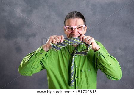 Stressed Man In Green Shirt Pink Glasses Biting In His  Necktie
