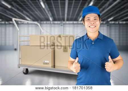 asian delivery man thumbs up in distribution warehouse