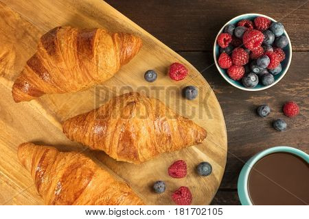 An overhead shot of crunchy French croissants with fresh raspberries and blueberries on a wooden cutting board, with a cup of hot chocolate