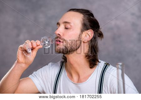 Young Man Drinking Clear Spirit