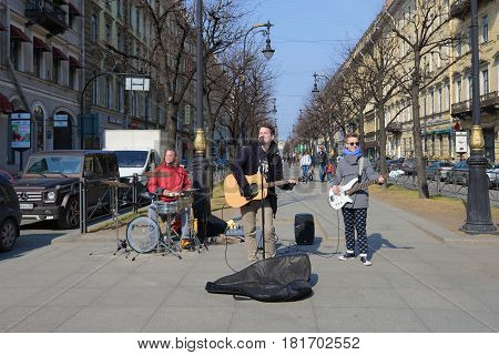 SAINT PETERSBURG, RUSSIA - APRIL 10, 2017: Young musicians play on the Bolshaya Konyushennaya street, sunny April day. Saint Petersburg