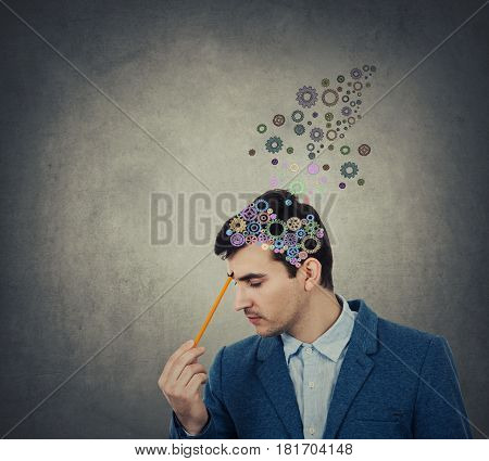 Successful businessman thinking and creating with a pencil pointed to his head a coloruful brain made from gear over his head setting goalslooking for the right answers.Creativity concept.Idea Concept